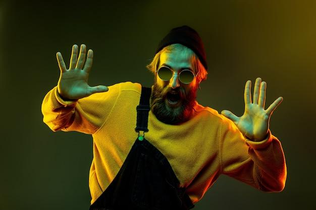 Retrato de uma mulher caucasiana em fundo gradiente de estúdio em luz de néon. lindo modelo masculino com estilo hippie em copos. conceito de emoções humanas, expressão facial, vendas, anúncio. chamada chocada.