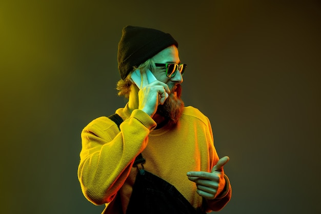 Retrato de uma mulher caucasiana em fundo gradiente de estúdio em luz de néon. lindo modelo masculino com estilo hippie em copos. conceito de emoções humanas, expressão facial, vendas, anúncio. falando ao telefone.