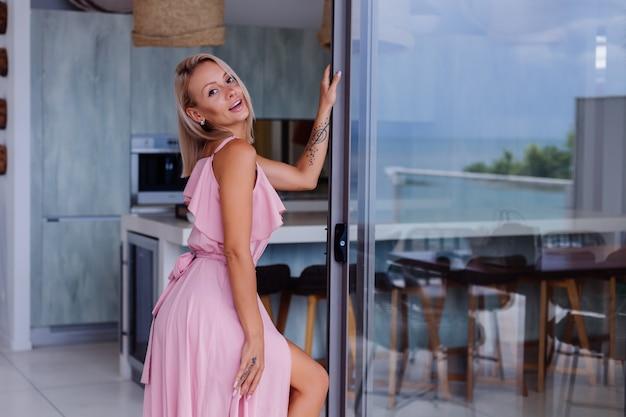 Retrato de uma mulher caucasiana em um vestido longo rosa elegante e romântico de férias em um hotel luxuoso e rico em uma villa com uma vista incrível de palmeiras tropicais. mulher com chapéu branco clássico