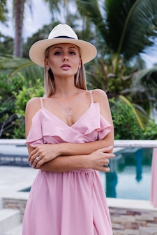 Retrato de uma mulher caucasiana em um vestido longo rosa elegante romântico de férias em um hotel luxuoso e rico, com uma vista incrível de palmeiras tropicais. mulher com chapéu branco clássico