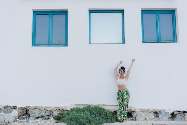 Retrato de uma mulher caucasiana feliz com os braços erguidos em frente a janelas azuis e uma parede branca durante o verão. estilo de vida ao ar livre
