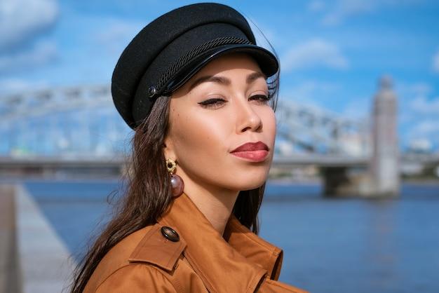 Retrato de uma mulher caucasiana feliz na margem do rio em um boné preto e jaqueta marrom.