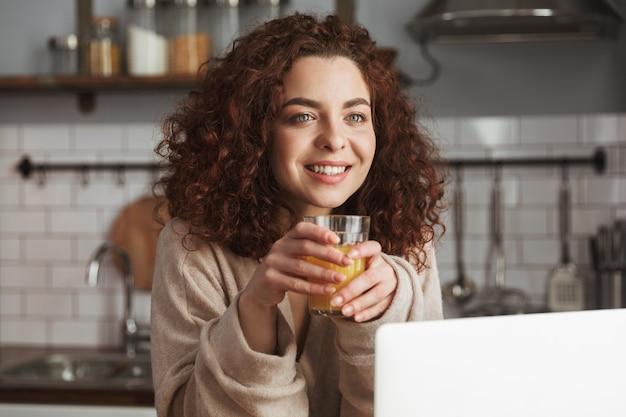 Retrato de uma mulher caucasiana feliz usando laptop na mesa no interior da cozinha, enquanto toma o café da manhã em casa