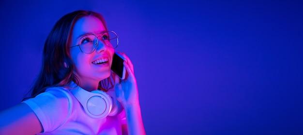 Retrato de uma mulher caucasiana isolado em um fundo azul em luz de néon multicolorida.