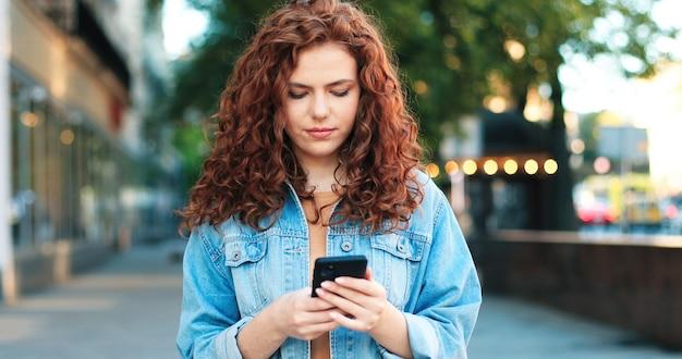 Retrato de uma mulher caucasiana ruiva calma, vestindo roupas casuais, olhando para a tela do smartphone em pé na rua verde, dia de primavera e mostrando os dentes para o largo sorriso
