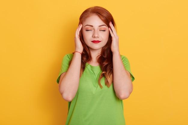Retrato de uma mulher charmosa e elegante em uma camisa verde, tendo dor de cabeça, tocando as têmporas com os dedos e fechando os olhos