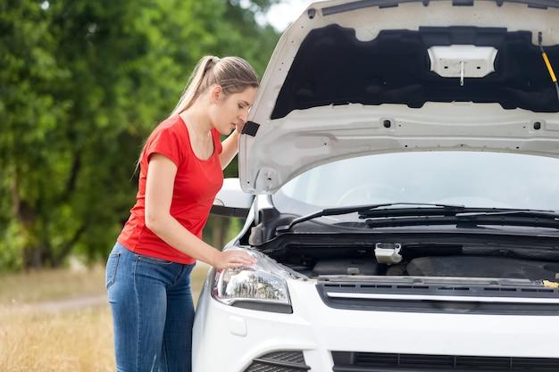 Retrato de uma mulher chateada olhando sob o capô de um carro superaquecido