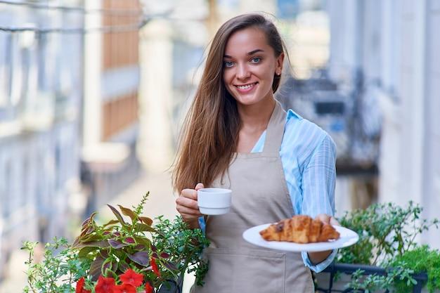 Retrato de uma mulher chefe de pastelaria bonita feliz fofa alegre sorridente com um prato de croissant fresco assado e uma xícara de café