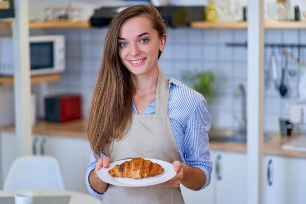 Retrato de uma mulher chefe de pastelaria bonita feliz fofa alegre sorridente com um prato de croissant marrom doce recém-assado