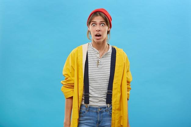 Retrato de uma mulher chocada olhando com olhos arregalados e boca aberta, posando contra uma parede azul, percebendo uma notícia horrorizada. jovem emocional com expressão de surpresa em roupas casuais