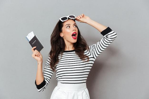 Retrato de uma mulher chocada, segurando o passaporte