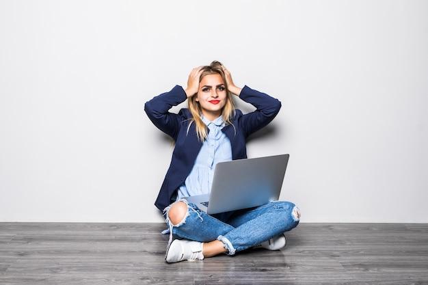Retrato de uma mulher chocada, sentada no chão com um laptop e olhando para uma parede cinza