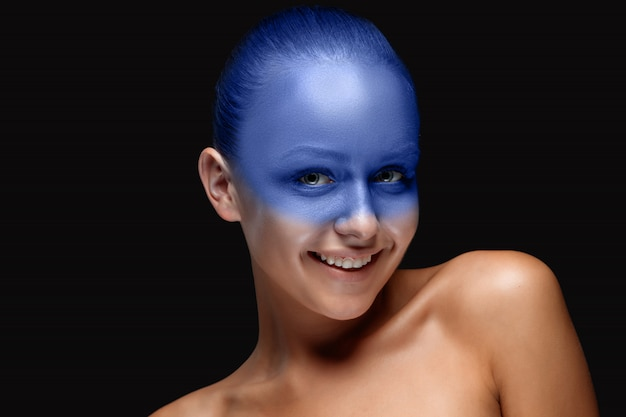 Retrato de uma mulher coberta com maquiagem artística azul