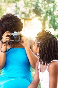 Retrato de uma mulher com afro tirando uma foto de uma menina. fotografia de conceito e aprendizagem.