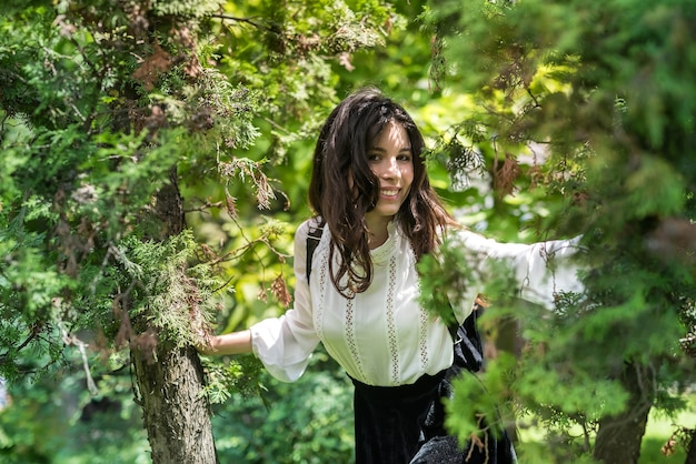 Retrato de uma mulher com blusa branca e saia preta elegante perto de uma árvore verde, parque da cidade