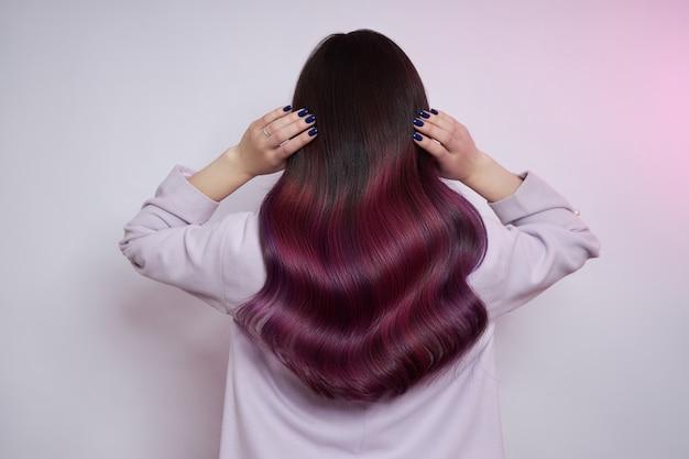 Retrato de uma mulher com cabelo voador colorido brilhante, todos os tons de roxo.