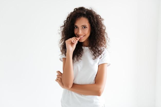 Retrato de uma mulher com cabelos cacheados, olhando para a câmera