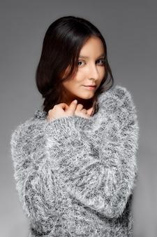 Retrato de uma mulher com cabelos lisos, embrulhando um suéter fofo