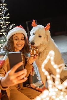 Retrato de uma mulher com chapéu de natal e xadrez com seu cachorro fofo, comemorando as férias de ano novo em casa, alimentando o cachorro com biscoitos de gengibre e fazendo selfie uma foto