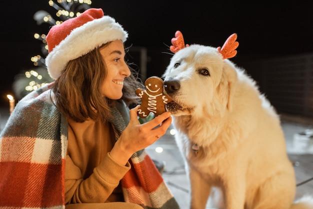 Retrato de uma mulher com chapéu de natal e xadrez com seu cachorro fofo, comemorando as férias de ano novo no terraço lindamente decorado de casa, alimentando o cachorro com biscoitos de gengibre