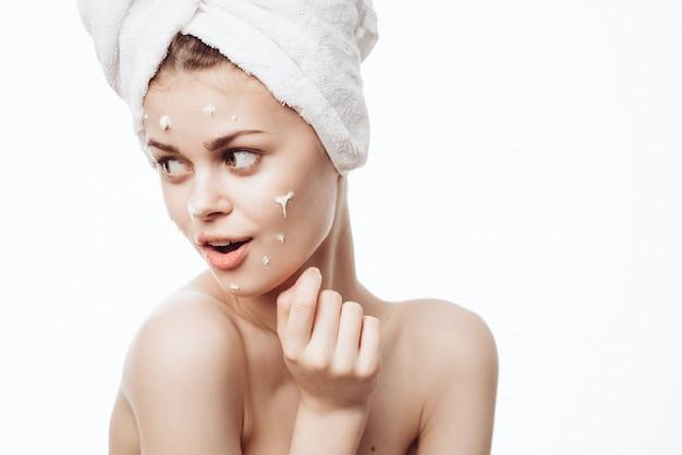 Retrato de uma mulher com creme para o rosto, cuidados com a pele, pele hidratante e nutritiva