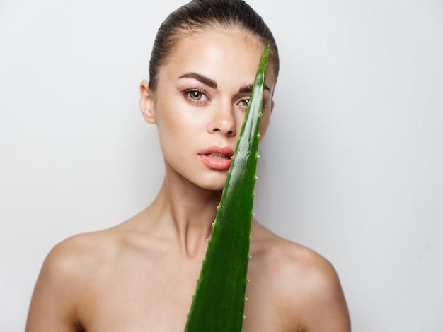 Retrato de uma mulher com folha de babosa verde, pele limpa, cosmetologia, aparência natural, modelo