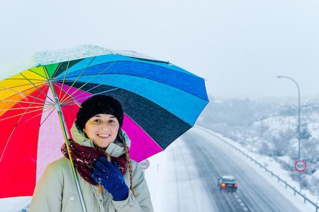 Retrato de uma mulher com guarda-chuva colorido em uma rodovia cheia de neve