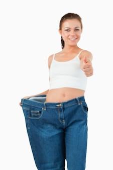Retrato de uma mulher com jeans muito grande com o polegar para cima