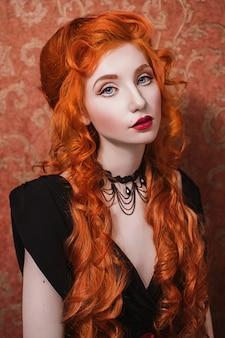 Retrato de uma mulher com longos cabelos cacheados vermelhos em um vestido preto e vermelho e gargantilha no pescoço. garota ruiva com pele pálida, olhos azuis