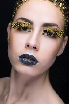 Retrato de uma mulher com maquiagem brilhante em fundo preto