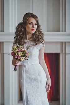 Retrato de uma mulher com maquiagem e um belo penteado em um vestido de noiva