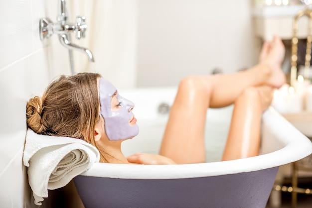 Retrato de uma mulher com máscara facial de alginato deitada na banheira retrô no banheiro