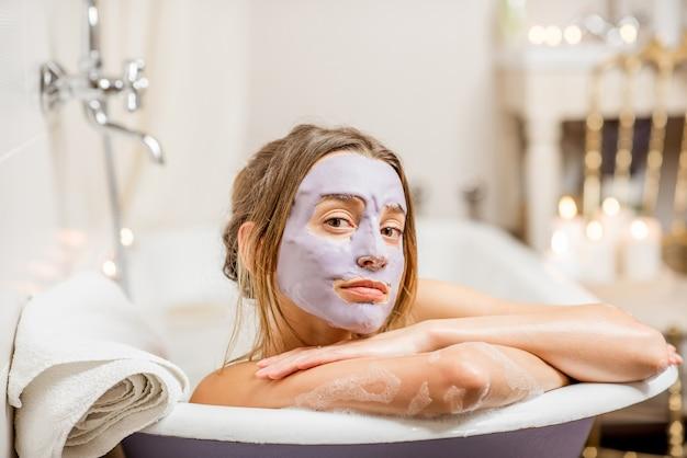 Retrato de uma mulher com máscara facial deitada na banheira retrô no banheiro