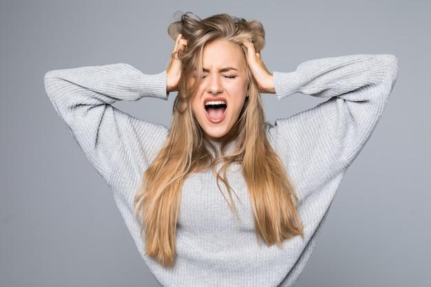 Retrato de uma mulher com raiva e frustrada, gritando em voz alta e puxando o cabelo dela, isolado no fundo cinza