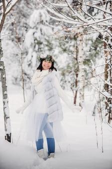 Retrato de uma mulher com roupas brancas em uma floresta fria de inverno. menina com uma coroa na cabeça em uma floresta de inverno coberta de neve