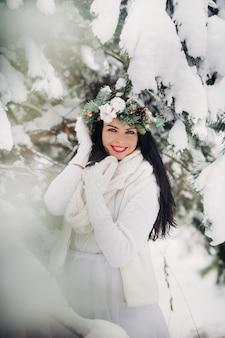 Retrato de uma mulher com roupas brancas em uma floresta fria de inverno. menina com uma coroa na cabeça em uma floresta de inverno coberto de neve.