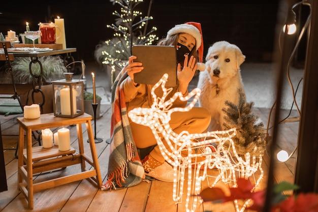 Retrato de uma mulher com seu cachorro fofo comemorando as férias de ano novo no terraço lindamente decorado de casa, tendo uma videochamada em um tablet digital
