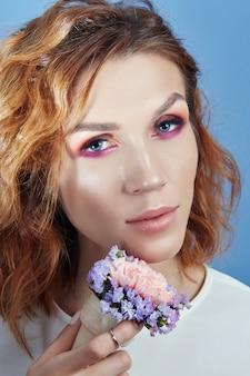Retrato de uma mulher com sombras vermelhas brilhantes nos olhos e maquiagem perfeita no rosto.