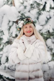 Retrato de uma mulher com um casaco de pele branco em uma floresta fria de inverno. menina com uma coroa na cabeça em uma floresta de inverno coberto de neve.