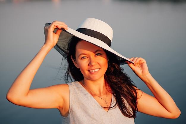 Retrato de uma mulher com um chapéu de palha, um retrato do close up de uma jovem sorridente no pôr do sol laranja.