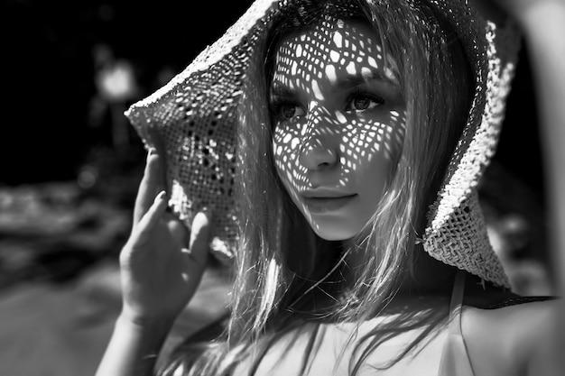 Retrato de uma mulher com um chapéu em uma foto preto e branco de fundo preto