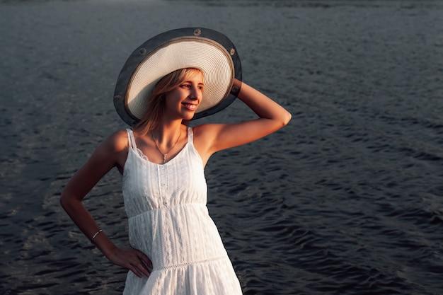 Retrato de uma mulher com um chapéu, uma bela jovem loira feliz em um vestido branco de verão e um chapéu de palha.