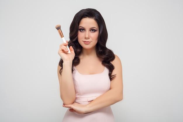 Retrato de uma mulher com um pincel de maquiagem na mão t.