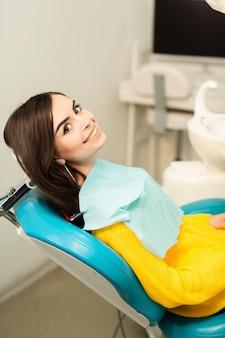 Retrato de uma mulher com um sorriso, sentado na cadeira odontológica no consultório odontológico