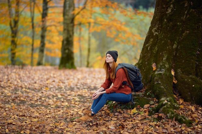 Retrato de uma mulher com um suéter, jeans e um chapéu debaixo de uma árvore na floresta de outono