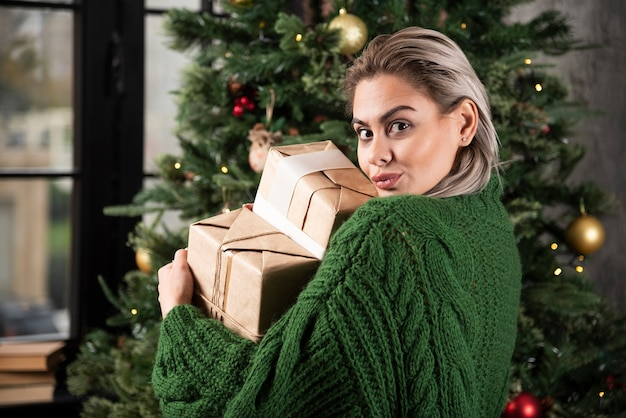 Retrato de uma mulher com um suéter verde segurando presentes