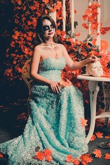 Retrato de uma mulher com uma maquiagem de fantasma se senta a uma mesa com uma cabeça de manequim.