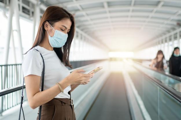 Retrato de uma mulher com uma máscara médica conversando com seu smartphone ao ar livre