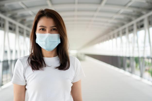 Retrato de uma mulher com uma máscara médica posando ao ar livre