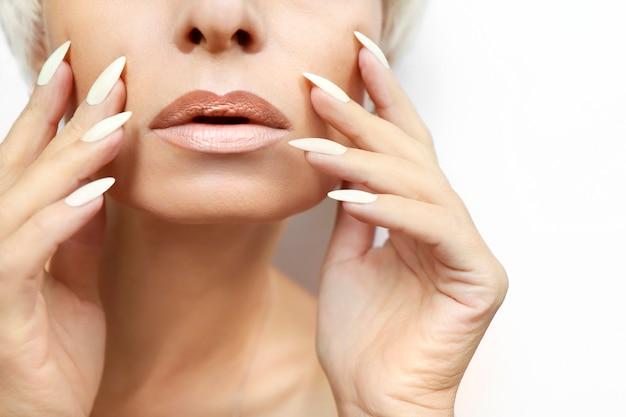 Retrato de uma mulher com uma pele limpa e saudável e uma longa manicure com esmalte de leite closeup.